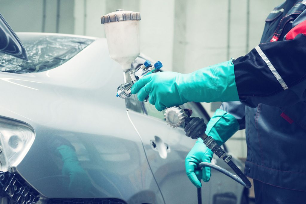 Auto serviceman painting a car